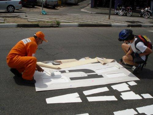 Gari e ciclista realizando juntos a pintura do asfalto