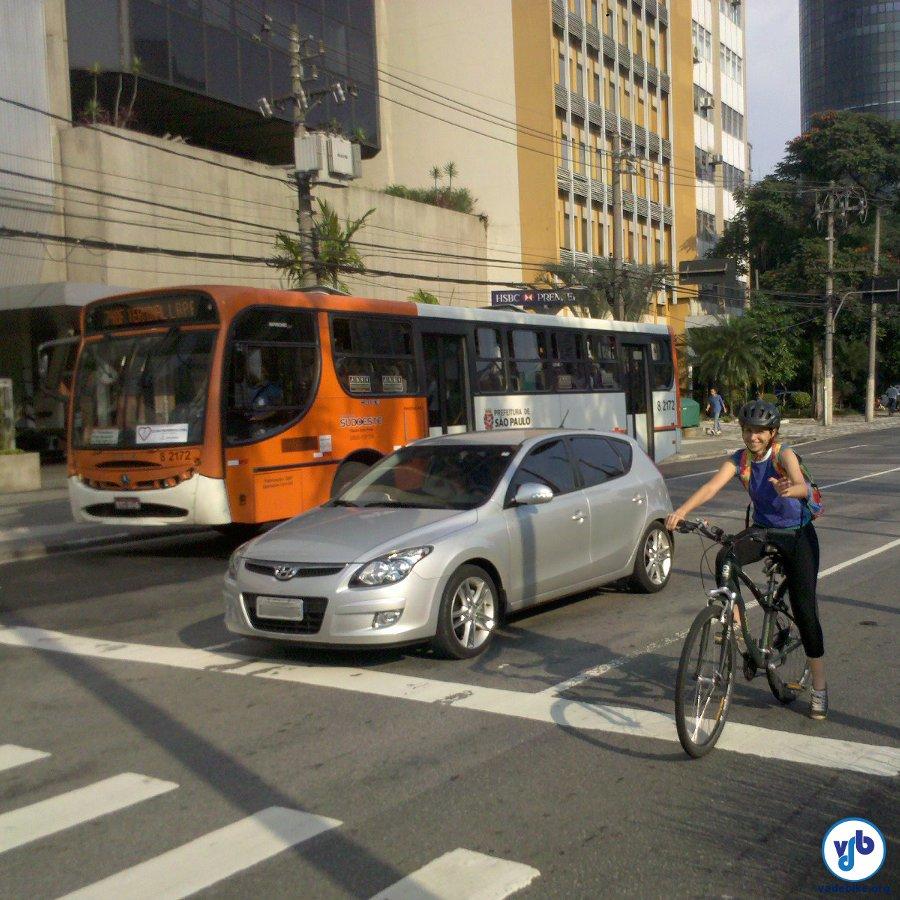 Ciclista na faixa da esquerda, aguardando o semáforo para acessar a ciclovia do canteiro central.
