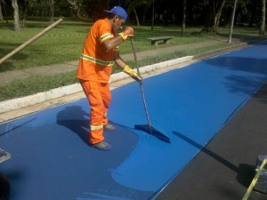 Trabalhador fazendo aplicação da tinta especial para pavimento de ciclovias, no Parque do Ibirapuera. Note que ela é espessa e precisa ser espalhada. Foto: Willian Cruz