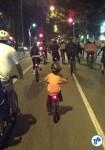 Criança pedalando na Bicicletada, protegida em meio à massa. Porque a rua deve ser de todos.