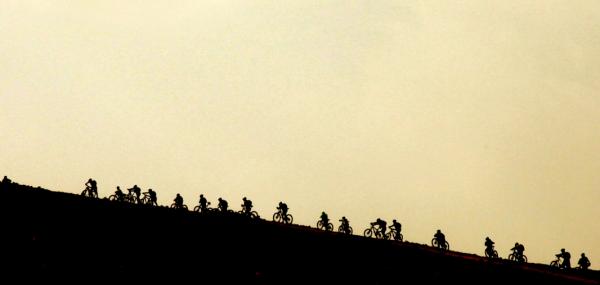 Ciclistas pedalando no deserto, durante o Wheels of Love. Foto: Divulgação