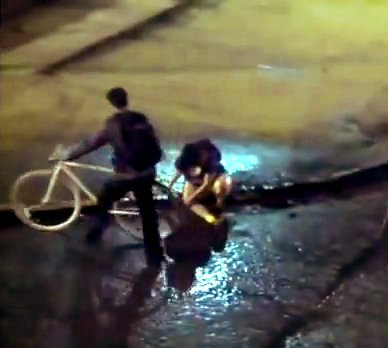 A moça que está sentada no meio-fio caiu quando a roda da bicicleta entrou numa sarjeta mata-ciclista. Veja aqui o cuidado que deve ser tomado com essas sarjetas.