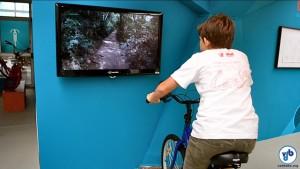 """Imagens feitas durante o """"Rolê de Bike"""" são exibidas em monitor, na bicicleta de rolo. Foto: Rachel Schein"""