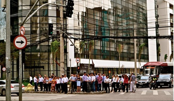 Pedestres aguardam para atravessar na região da Berrini, bairro que abriga muitos prédios comerciais em SP. Foto: Rachel Schein