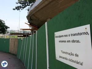 Placa em tapume dento do Parque pede desculpas pelo transtorno. Ao fundo, a estrutura da ciclopassarela. Foto: Willian Cruz