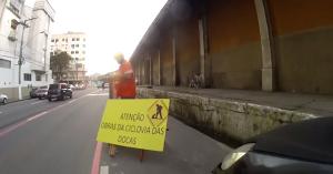 """Ciclistas utilizaram equipamentos de segurança e criaram placa """"semi-oficial"""" indicando obras na pista. Foto: Reprodução"""