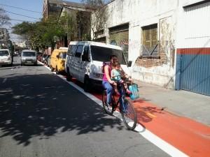 Mãe e criança indo para a escola são colocadas em risco por carros estacionados na ciclovia. Foto: Paulo Preto