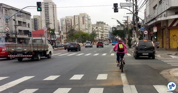 """Ciclista pedala em trecho sem ciclovia da Av. Domingos de Morais. Em suas costas, o cartaz que diz: """"respeite, um carro a menos"""". Foto: Willian Cruz"""