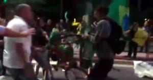 Em meio a socos e xingamentos de uma multidão enfurecida, um casal com uma bicicleta vermelha. Imagem: Warley Alves/Reprodução