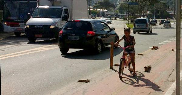 Menina pedala sozinha na ciclovia da Avenida dos Metalúrgicos: alguns parecem preferir que ela estivesse em meio aos carros. Foto: Felipe Claros